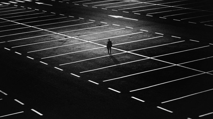 Black and White Photograph. Person standing alone in a parking lot, low lighting.