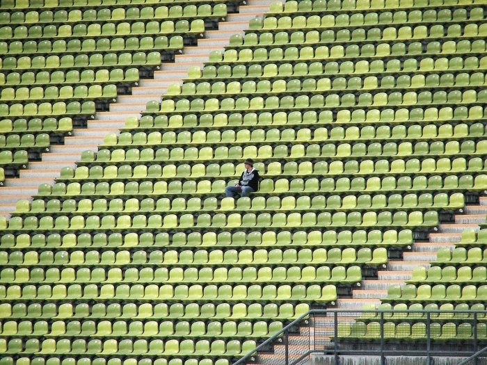 Man wearing denim pants and a hat is sitting alone in the middle of a stadium in the bleachers. The seats are varying shades of green.